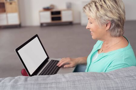 citizen: Side View of a Happy Senior Woman Using her Laptop Computer While Relaxing at the Couch In the Living Room Stock Photo