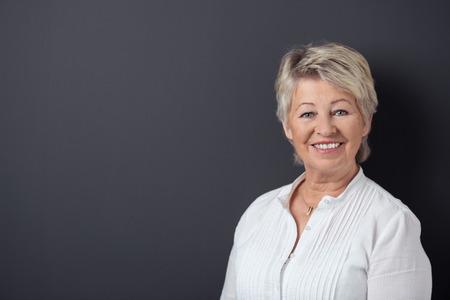 Taille-up van aantrekkelijke lachende senior blonde vrouw draagt wit overhemd, camera kijken op een zwarte achtergrond