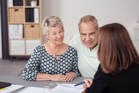 Middle Aged Couple Listening to a Female Agent Discussing Some Business to them at the Table.