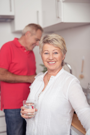 60 years: Close up Happy Matured Housewife Holding a Glass of Water at the Kitchen and Smiling at the Camera Stock Photo