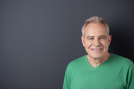 age 60: Portrait of a Smiling Senior Man in Casual Green Shirt Against Gray Wall Background with Copy Space on the Left Side. Stock Photo