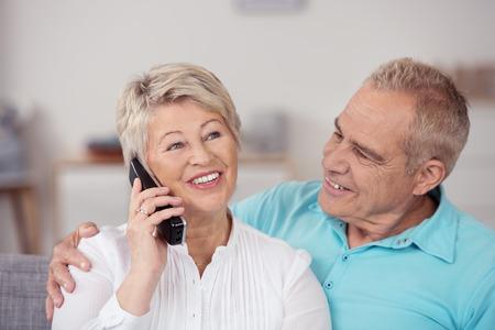 Close up Süße Middle Aged Mann Blick auf seine hübsche Frau im Gespräch mit jemandem am Telefon. Standard-Bild