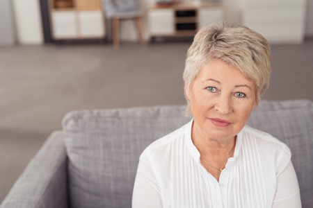 Close up Aged Blond Moyen femme assise sur Gris Couch tout en regardant la caméra Banque d'images - 41689964