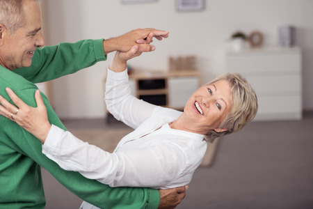 Happy Sweet Senior Couple Dancing Slow Ballroom Dance Inside the House During their Leisure Time.