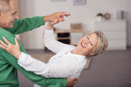 taniec: Szczęśliwy Słodka para starszych taniec powolny taniec towarzyski w domu Podczas Fitness. Zdjęcie Seryjne