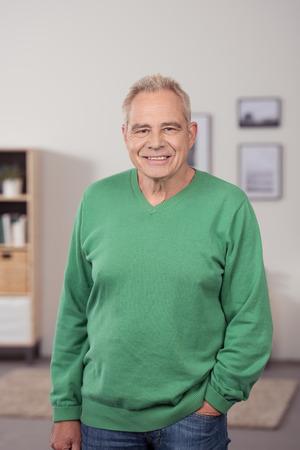 Hombre mayor sonriente de pie relajado en su sala de estar con la mano en el bolsillo mirando a la cámara Foto de archivo - 41689971