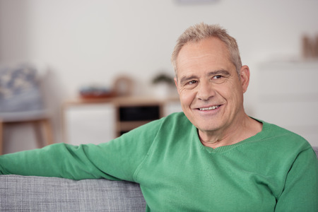 Close up Smiling Middle Aged Man in Casual Green Shirt, Sitting at the Sofa While Looking Into Distance and Thinking of Something Stock Photo