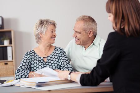 personas hablando: Senior pareja sonriente dulce mutuamente mientras Hablar con un agente femenino dentro de la oficina.