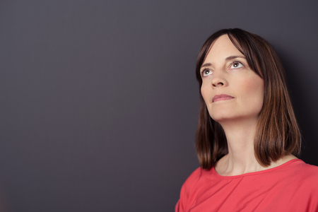 adult wall: Close up Pensive Adult Woman Against Gray Wall Background with Copy Space, Looking Up Seriously Stock Photo