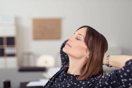 head tilted: Businesswoman taking time out at work relaxing in her chair at the office with her head tilted back on her clasped hands and eyes closed