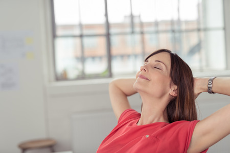 Promyšlený Office Žena opírající se ji zpátky na židli s rukama drží zadní části její hlavy a oči jsou zavřené, s důrazem na relaxaci po práci. Reklamní fotografie