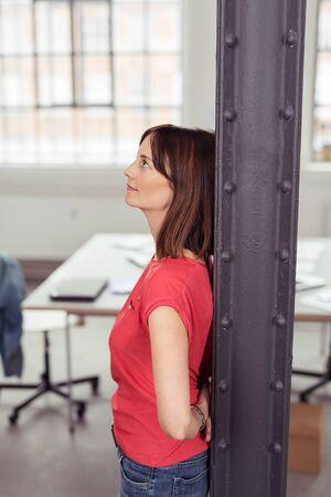 emphasising: Riflessivo donna adulta che si appoggia la schiena contro metallo postale All'interno dell'Ufficio durante la ricerca, sottolineando di pensare qualcosa di grave. Archivio Fotografico