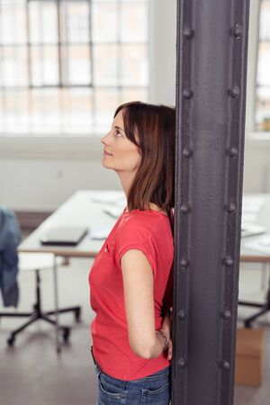 metal post: Thoughtful Adult Woman Leaning her Back Against Metal Post Inside the Office While Looking Up, Emphasizing of Thinking Something Serious. Stock Photo
