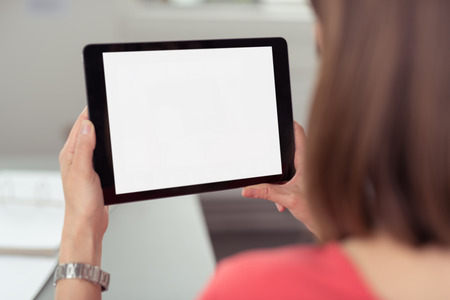 Woman sitting and using a black wireless tablet PC with white blank touch screen or interface, rear Stockfoto