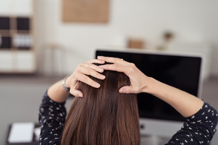 Rear View of a Worried Office Woman Holding her Head In Front her Powered Off Computer Due to Power Interruptions. Stockfoto