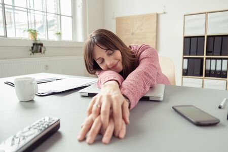 laying down: Businesswoman taking a relaxing break stretching her hands across the desk in front of her and laying down her head with a smile of contentment and eyes closed