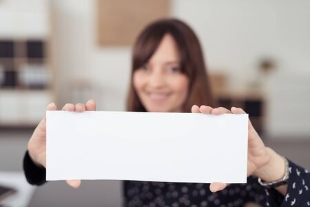 office space: Smiling Office Woman Holding White Paper with Copy Space Using Both Hands and Showing at the Camera.
