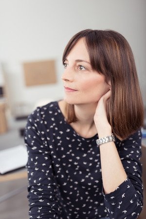 brunette woman: Close up Thoughtful Office Woman at her Desk Looking to the Left of the Frame While Leaning on her Hand. Stock Photo