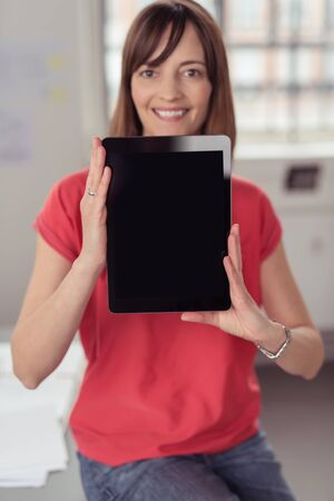 one person: Smiling Woman Holding her Portable Tablet Computer and Showing the Black Empty Screen at the Camera, Emphasizing Copy Space. Stock Photo