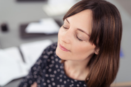 Close up Smiling Thoughtful Office Lady, Sitting at her Desk, Thinking So Deep with Eyes Closed. Stock Photo