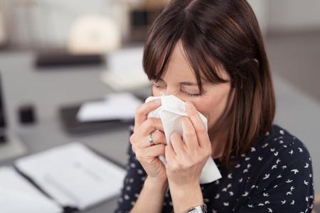 enfermo: Close up Enfermo joven señora de la oficina en su escritorio estornudos en un pañuelo blanco con los ojos cerrados.
