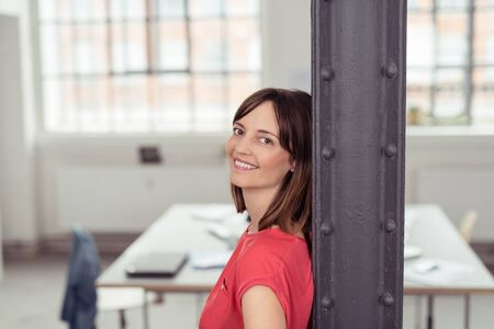metal post: Cheerful Adult Woman Leaning her Back Against Metal Post Inside the Office, Smiling at the Camera. Stock Photo