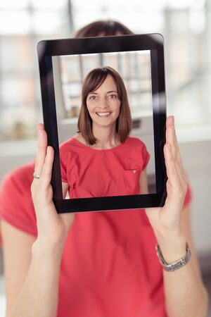 concealing: Woman holding up a selfie on a tablet computer concealing her face with a happy smiling image of herself