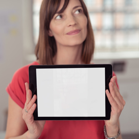 emphasizing: Close up Thoughtful Woman Holding her Tablet Computer While Showing the Empty White Screen at the Camera, Emphasizing Copy Space.