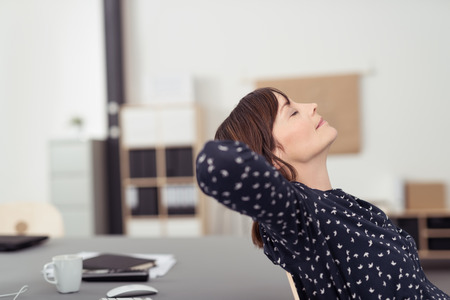 office break: Tired Office Woman at her Worktable, Leaning her Back on a Chair with Hands at the Back of her Head and Eyes Closed, Emphasizing of Thinking Something.