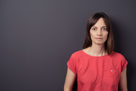 adult wall: Close up Serious Adult Woman in Casual Red Shirt Against Gray Wall Background with Copy Space, Looking at the Camera.