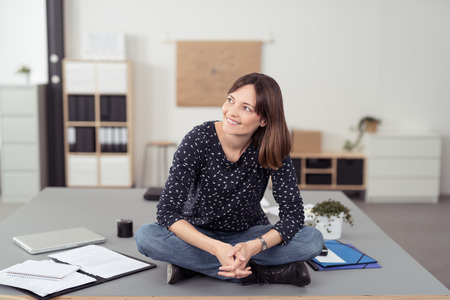 Cheerful Office Woman Sitting on the Boardroom Table with Legs Crossed While Looking Into Distance. Stock Photo