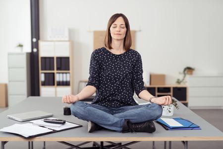 健康局女性がカメラの前でヨガの練習をしながら、会議室のテーブルの上に座って。