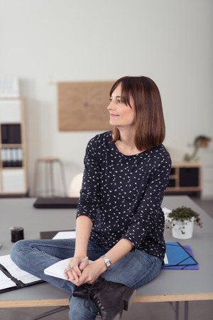 cross legs: Smiling Thoughtful Office Woman Sitting on a Boardroom Table with Cross Legs, Looking into Distance.