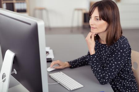 persona de pie: Mujer Bonita Oficina Sentado en su escritorio, Usar el ordenador mientras se inclina en su codo serio.