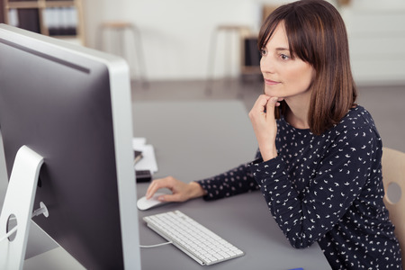 personen: Pretty Office Zitting van de vrouw op haar bureau, met behulp van de computer terwijl leunend op haar elleboog Serieus.