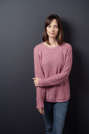 adult woman: Portrait of a Serious Woman in Trendy Clothing, Standing Against Gray Wall While Holding her Other Arm and Looking Straight at the Camera.