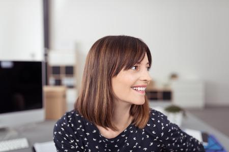 ouvrier: Close up heureux jeune femme avec Bureau Cheveux bruns, Assis à sa table tout en regardant vers la droite du cadre.