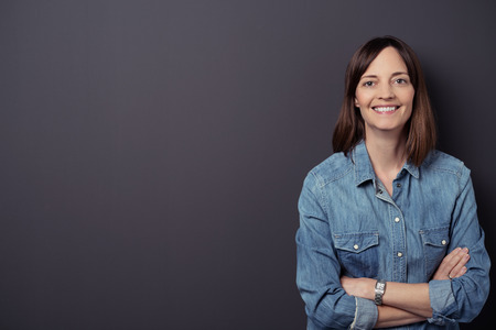 employee satisfaction: Half Body Shot of a Cheerful Woman in Denim Shirt, Smiling at the Camera with Arms Crossed Against Gray Wall Background with Copy Space.