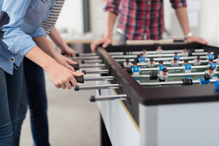 Employees Playing Table Soccer Indoor Game in the Office During Break Time to Relieve Stress from Work.