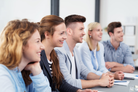 Team van vijf Glimlachende Jonge Beambten Zittend aan de Boardroom tafel, op zoek naar rechts van het frame tijdens het luisteren naar iemand.