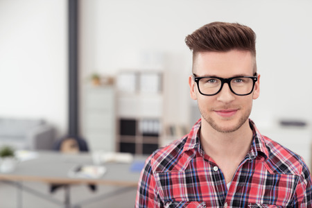 Close up Handsome Young Man with Eyeglasses Smiling at Camera Inside the Office. Stock Photo