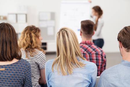 ENTRENANDO: Vista posterior de los jóvenes empleados de oficina en una reunión de negocios dentro de la oficina, escuchando a alguien presentación de algo. Foto de archivo