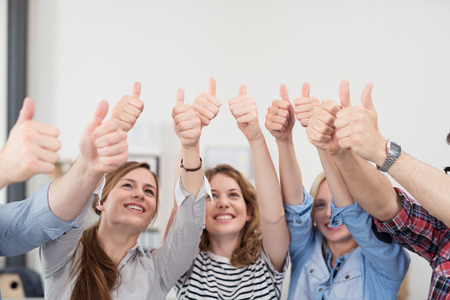 Team of Five Young Business People Inside the Office, Showing Thumbs Up Signs with Happy Facial Expressions.