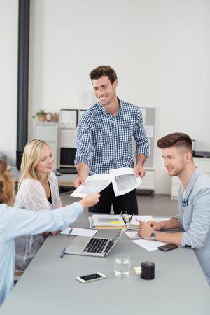 LIDER: Hermoso L�der del Equipo Distribuir algunos documentos a los Miembros mientras que haciendo un Encuentro Empresarial Dentro de la sala de juntas Foto de archivo