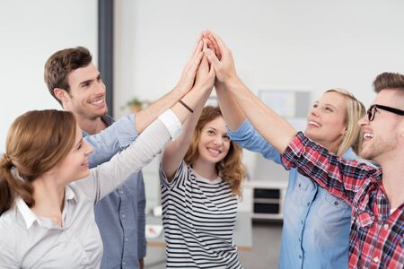 Five Young Office Workers Inside the Office, Raising their Hands at the Center Together with Happy Facial Expressions.