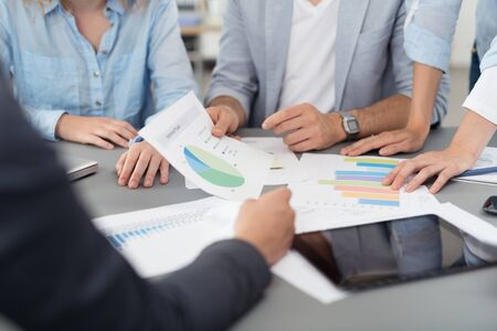 workers group: Various Business Documents with Charts and Figures on Top of the Table During the Meeting of the Executives. Stock Photo