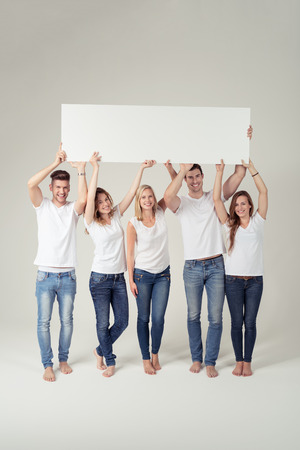 empty of people: Team of Happy Young People in Casual White Shirts and Blue Jeans, Holding an Empty Rectangular Board with Copy Space Up. Captured in Studio with Off-White Background.