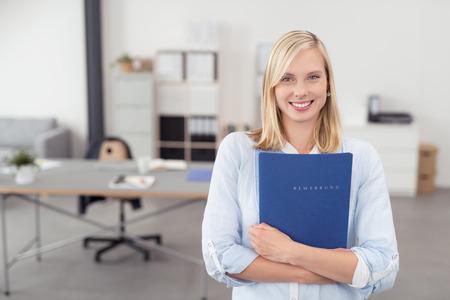 예쁜 금발 젊은 사무실 여자는 블루 문서 폴더를 포옹하고 사무실 내부 미소를 카메라.