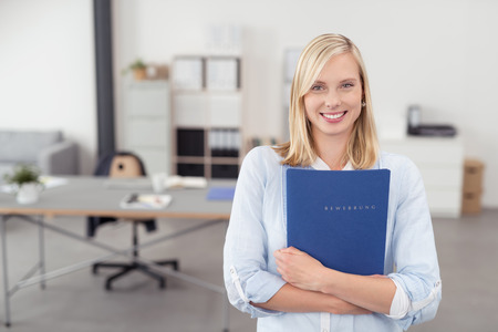 Pretty Blond Young Office Woman Hugging a Blue Documents Folder and Smiling at the Camera Inside the Office. Archivio Fotografico