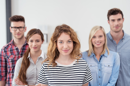 Half Body Shot of Five Young Business People in Casual Clothing Inside the Office, with Young Female Leader, Smiling at the Camera